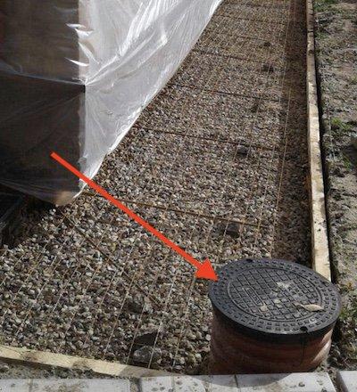 Красной стрелкой на фотографии указан смонтированный дренажный колодец. Стадия строительства дренажа - обустройство отмостки фундамента.